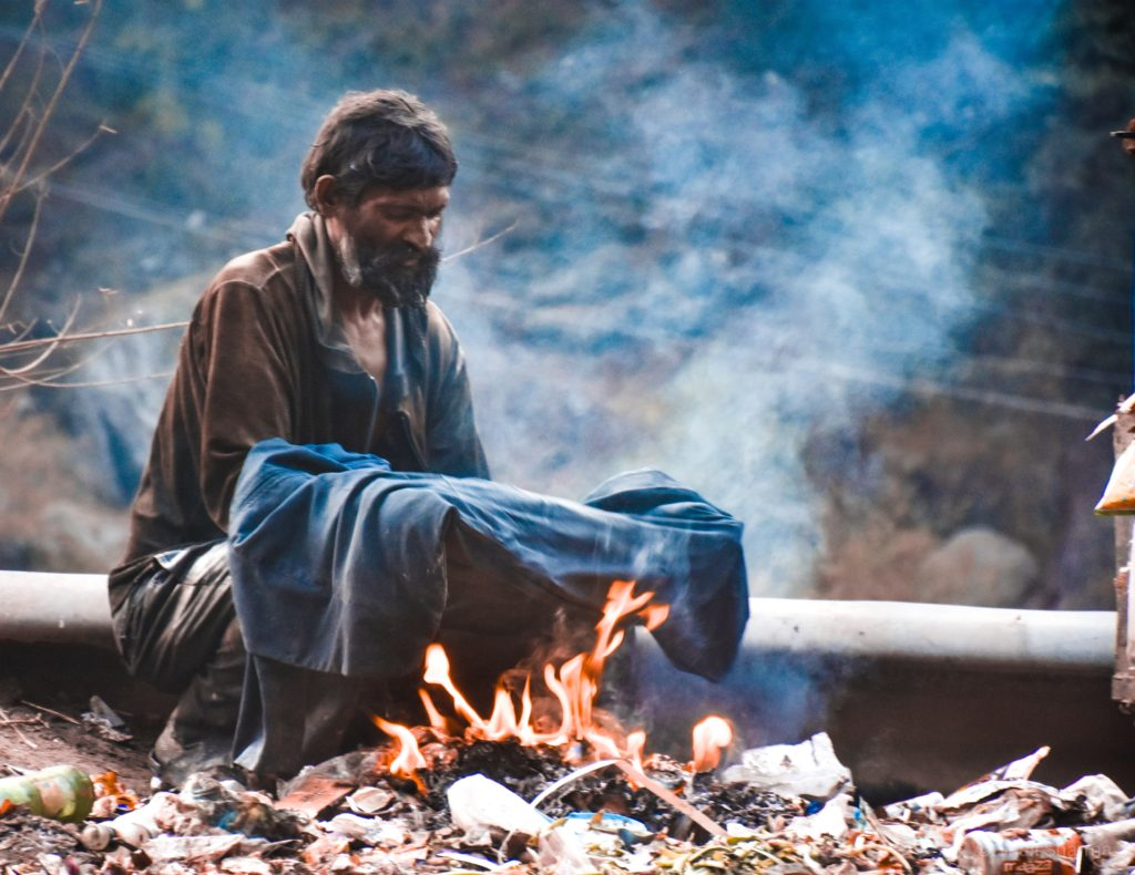 homeless man dries clothes over fire